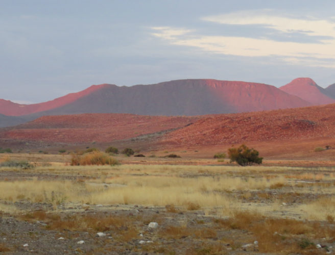 Goldt, tørst landskap med rødt fjell og gul bakke.