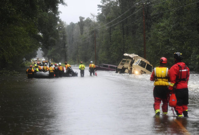 En vei er oversvømmet. Redningsmannskap er på plass for å få biler opp av grøfta.