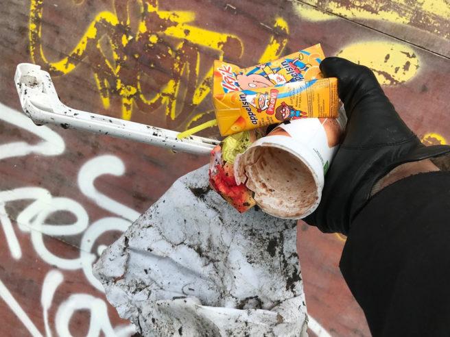 Nærbilde av en hånd, med svart hanske, som holder et tomt plastkrus og diverse annet plastavfall.