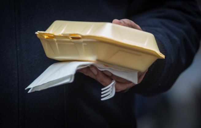 Hånd som holder plastbestikk og isoporbeholder til take-away.