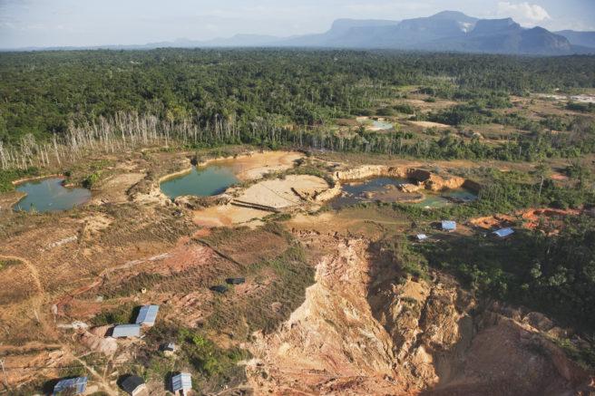 En gruve fremstår som et stort sår i landskapet. Rundt står skogen og viser tydelig hvilken natur som er rasert for grave.