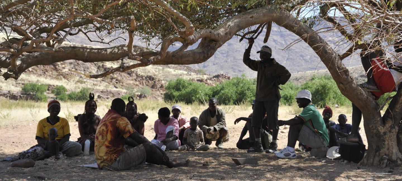 Lokalbefolkningen samles under et tre i Namibia, for å diskutere driften av det lokaldrevne naturreservatet.