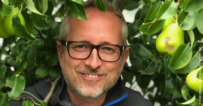 Bård Vegar Solhjell har vært generalsekretær i WWF Verdens naturfond siden 1. mars 2018. Her titter han ut mellom grønne blader.