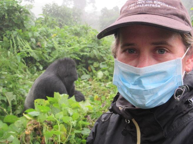 WWF-rådgiver Melissa de Kock ikledd munnbind med en gorilla i bakgrunnen under et besøk i Virunga nasjonalpark