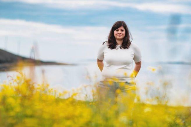 Karoline Andaur står foran en blomstereng med havet i bakgrunnen