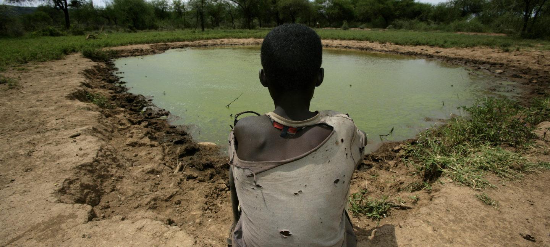 En afrikansk gutt sitter og ser på lite vannhull.