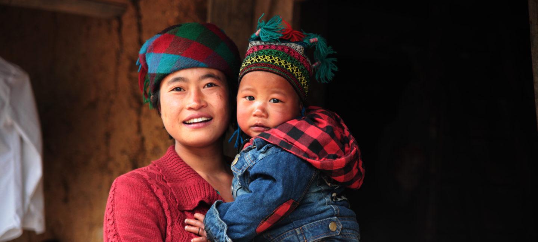 Mor og barn står foran huset sitt i en landsby i panda landskap i Kina.