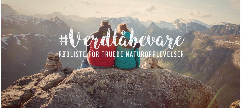 To personer holder rundt hverandre mens de sitter på toppen av fjellet med utsikt utover andre fjelltopper.