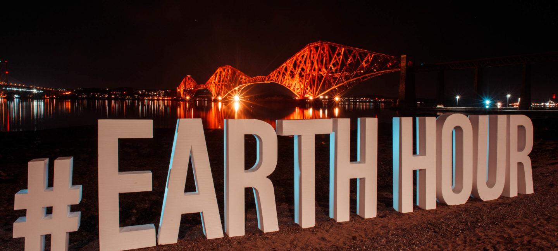 Noen få lyskjegler lyser opp en bro mot mørkt hav. I forgrunnen ruver bokstavblokker som former ordet Earth Hour
