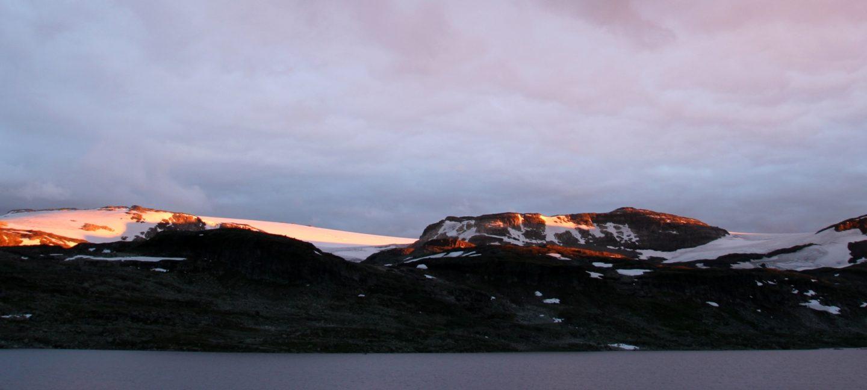 Hardangerjøkulen i seinsommersolnedgang. Snødekte topper på mørke fjellsider, lyst opp av de siste solstrålene, grå sjø under og grå himmel over.