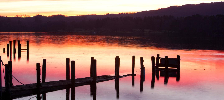 Den rødglødende solnedgangen speiler seg i en blikkstille innsjø.
