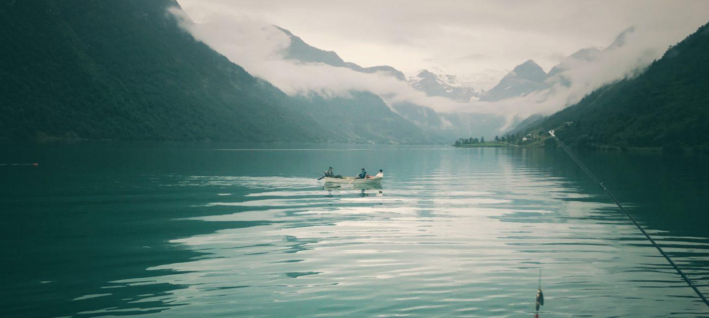 En robåt med tre mennesker i en overskyet fjord