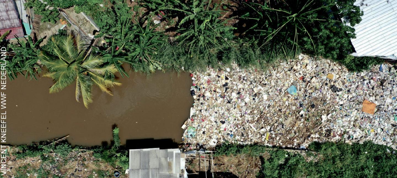 En elv fylt med plast sees ovenfra.