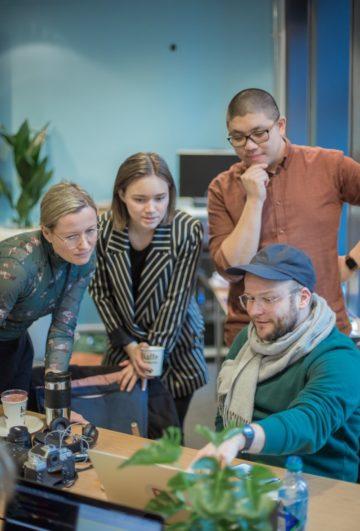 Tre mennesker ser på en utvikler som peker på PC-skjermen sin og forklarer.