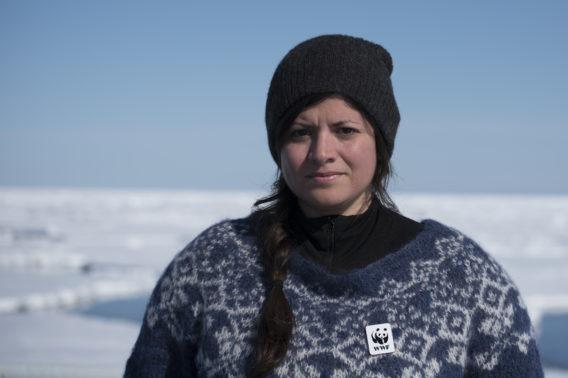 Karoline Andaur foran et snødekket landskap, iført strikkegenser og lue, og med en WWF-pin festet til genseren. Ser alvorlig ut.