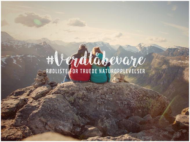 Et kjærestepar på en fjelltopp som ser utover et vakkert landskap.