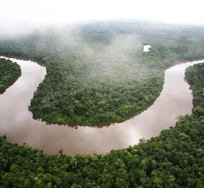 En elv i Amazonas sees mellom grønne trær og under skyer