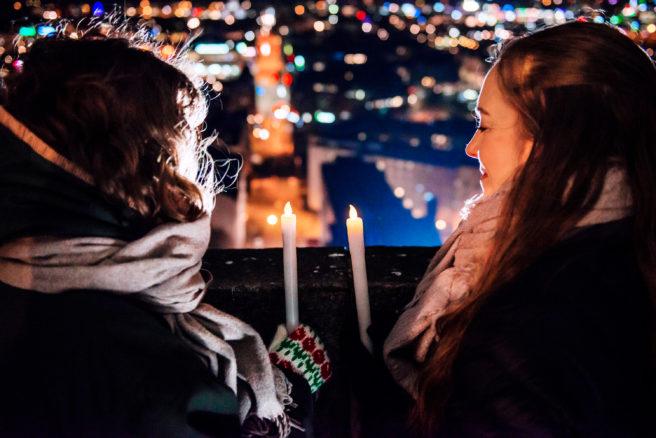 To jenter avbildet bakfra mens de ser utover en by, på kveldstid og med et stearinlys hvert i hånden