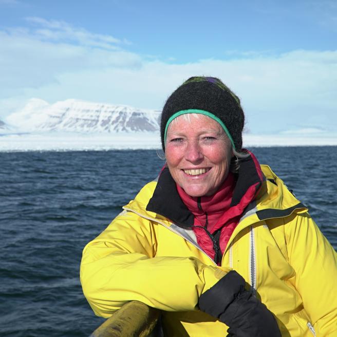 Kari lener seg mot rekkverket på en båt. Hun har gul regnjakke og lue, det er kaldt. Det er et snødekket fjell i bakgrunnen på bildet.