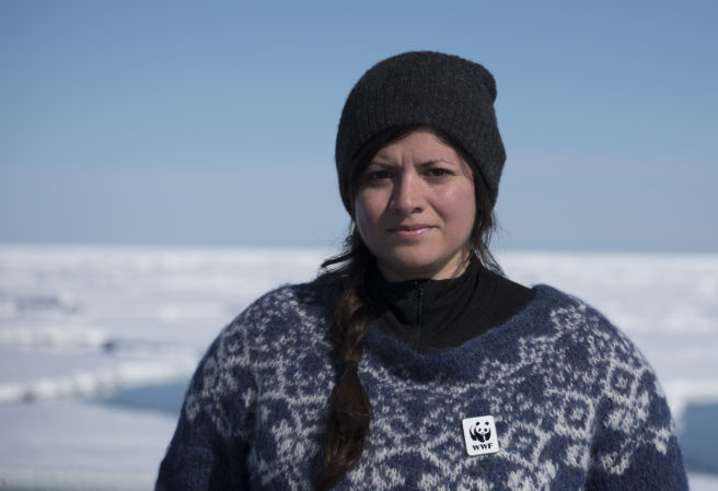 Karoline Andaur foran et snødekket landskap, iført strikkegenser og lue, og med en WWF-pin festet til genseren. Ser alvorlig ut