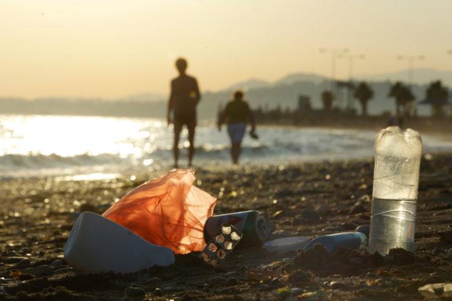 Plastforsøpling på stranden, siluetter av mennesker i bakgrunnen