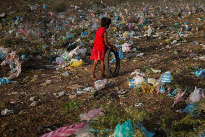 Et lite barn triller et dekk på en bakke full av plastsøppel.