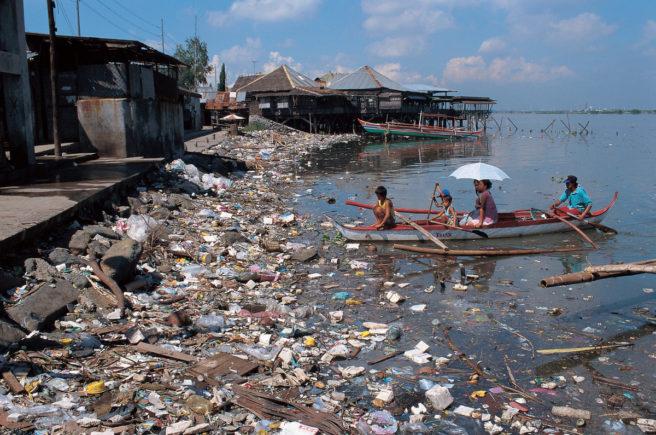 En liten båt med mennesker omgitt av store mengder plastforsøpling på Filippinene.