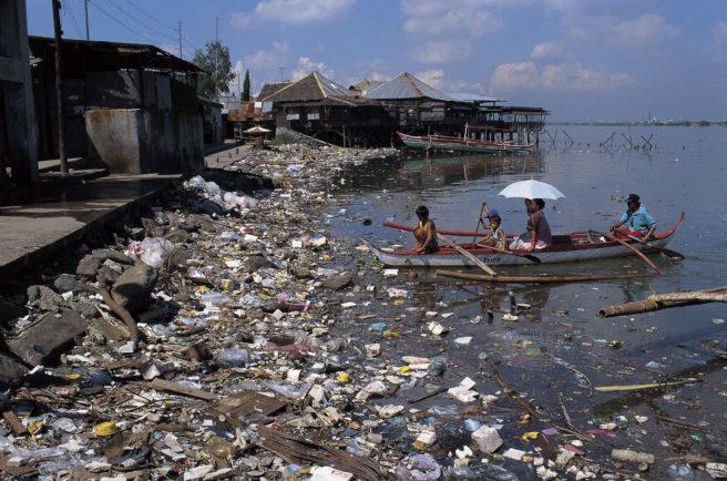 To barn og tre voksne i en liten båt som seiler mot kaien, som er full av plast og annen søppel