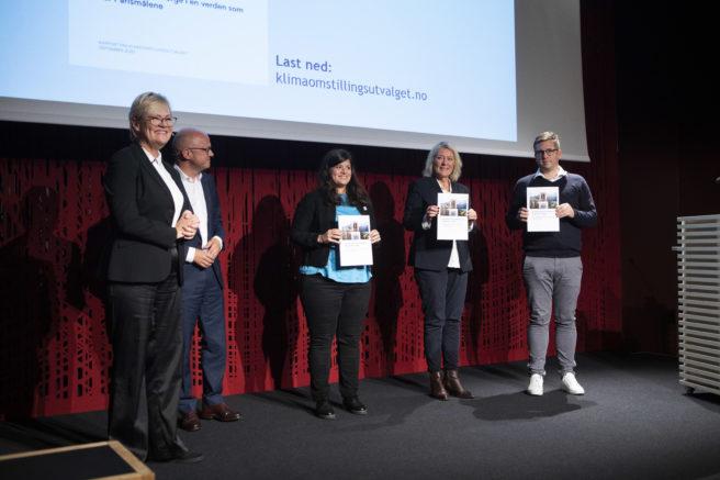 Bilde fra pressekonferansen, fem mennesker står på rekke på scenen med rapporten foran seg