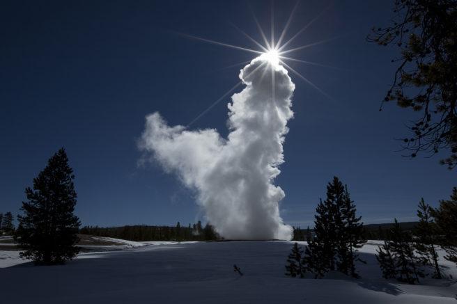 Vanndamp står mot en blå himmel og solen dekkes av dampen