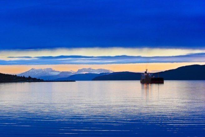 En båt på et hav i solnedgang.