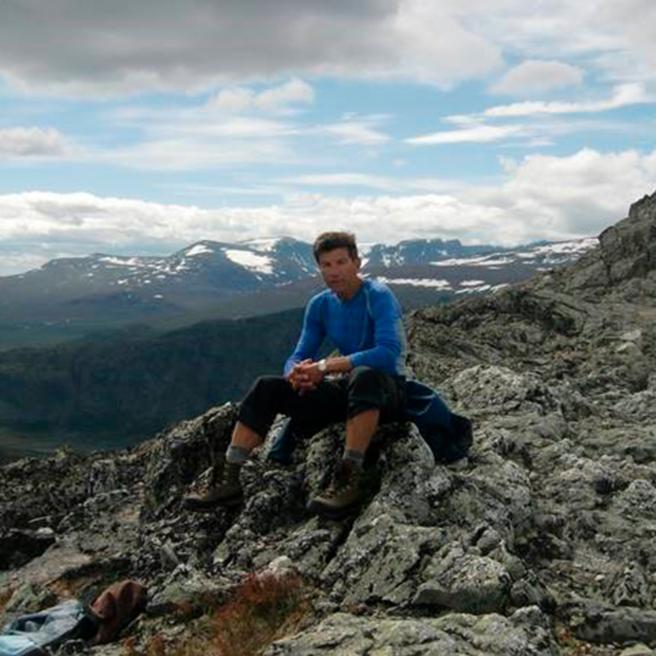 Dag sitter på en fjelltopp, med andre fjelltopper i bakgrunnen. Han har blå genser. Det er fint vær.