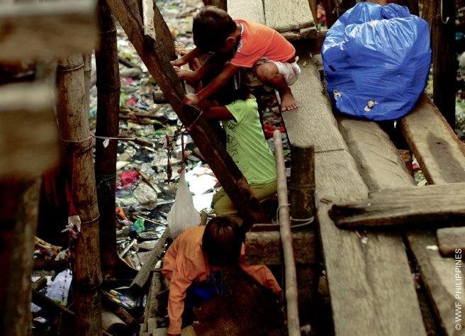 Filippinske barn klatrer på en bro eller kai over en vannoverflate dekket helt av plast.