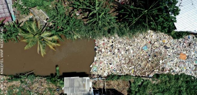 En elv sees ovenfra, der halve er full av søppel.