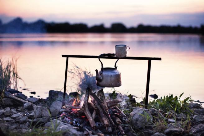 Kaffekjele og kopp henger over brennende bål ved vannet i solnedgang.