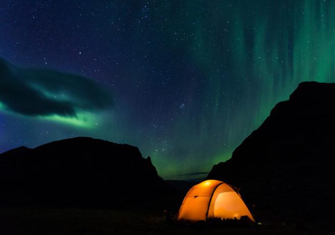 En ensomt telt under en himmel full av nordlys