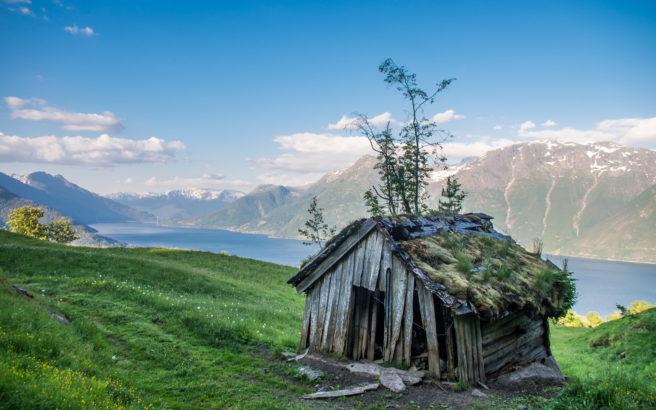 Gammel seter som står på bratt jorde med fjord i bakgrunnen