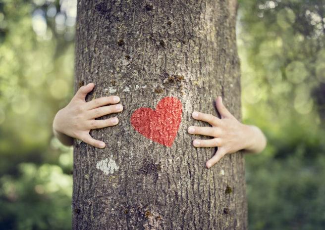 Illustrasjonsbilde av et barn som klemmer et tre med et påmalt hjerte.