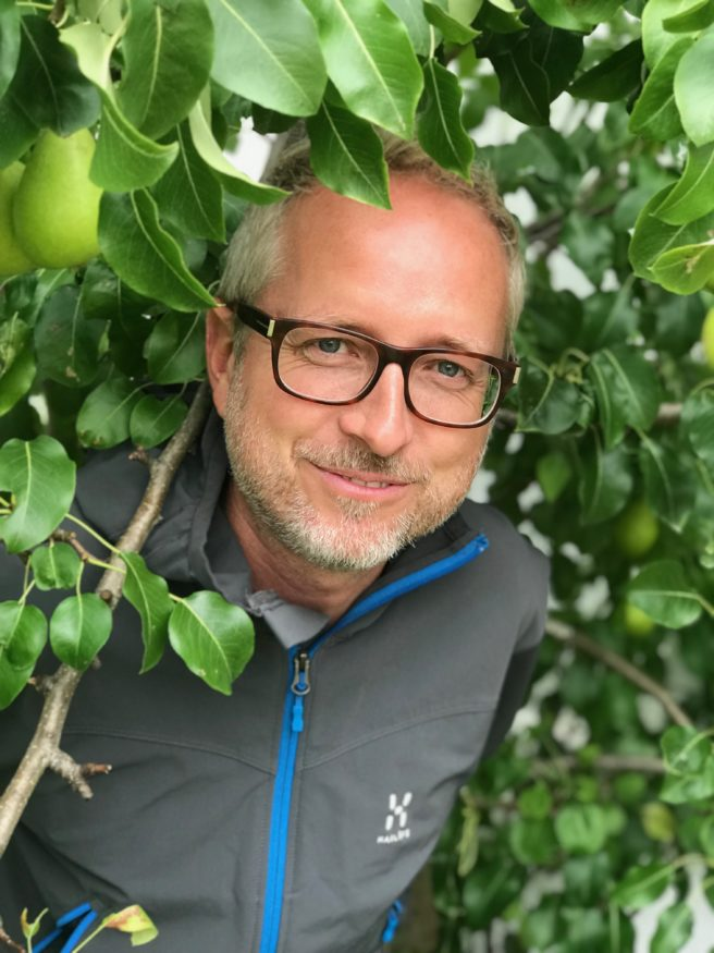 Bård Vegar Solhjell titter frem fra en busk.